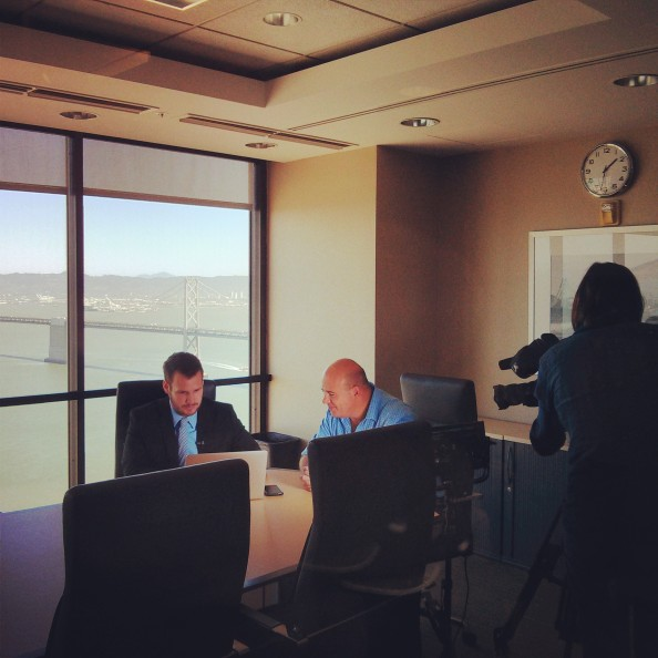Behind the scenes photo of Jered Kenna and Alastair Leithead talking about Bitcoin in the Tradehill Conference Room.